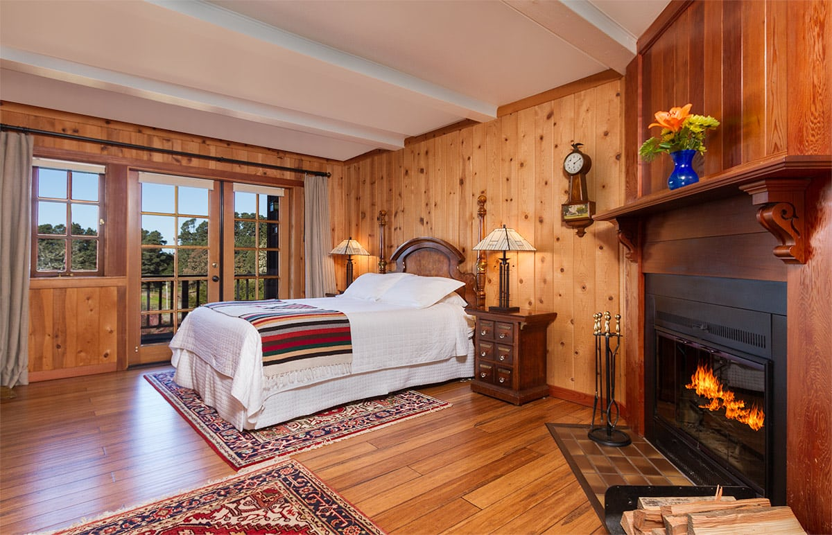mendocino coast bed and breakfast with ocean views, fireplace, red couch and queen bed