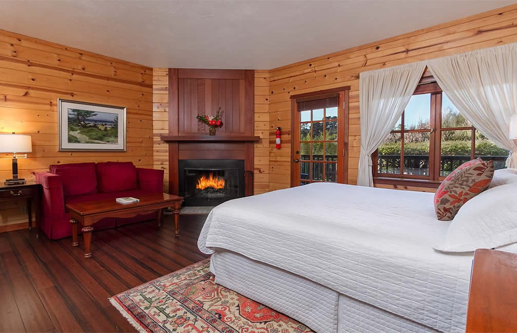 mendocino coast bed and breakfast with ocean views, fireplace, red couch and king bed