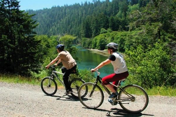 mendocino vacation packages: couple bikes along big river